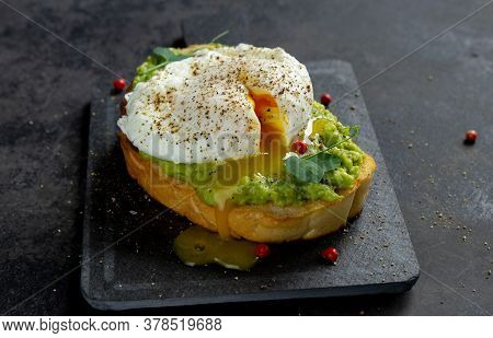 Yolk From Poached Egg On Avocado Cream And Bread Toast On Dark Background