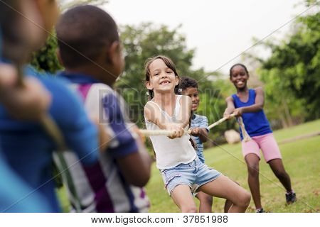 Happy School Children Playing Tug Of War With Rope In Park