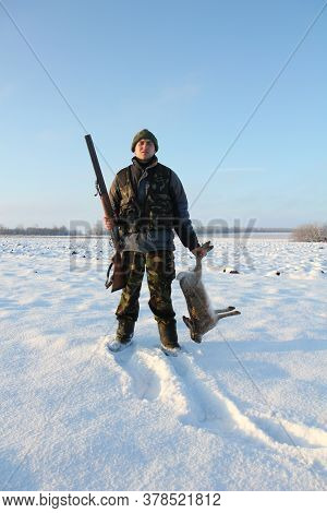 Winter Hunting. A Hunter In A Camouflage Suit And With A Gun Holds A Hare Trophy In His Hands. A Man