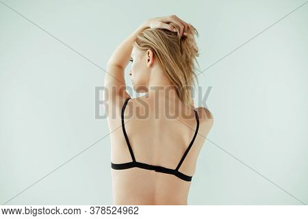Back View Of Young Woman In Black Bra Touching Hair Isolated On Grey