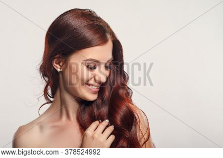 Studio Glamor Portrait Of A Beautiful Woman With Luxurious Hair On A Light Background. Place For Cop
