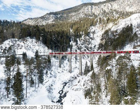 Filisur Switzerland - January 31. 2019: A Red Passenger Swiss Train Passing On The Schmitten Viaduct
