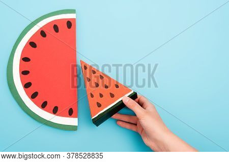 Partial View Of Female Hand With Paper Watermelon Slices On Blue Background
