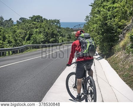 Active Man With Backpack Riding Bicycle On Roadside Of Asphalt Road At Sunny Summer Day