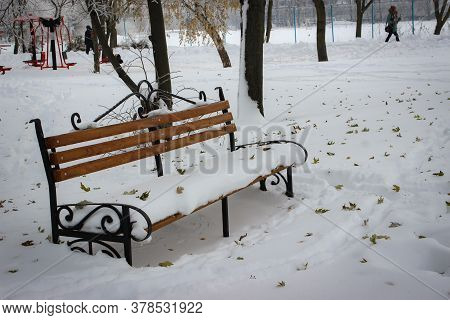 In The Winter Park, An Empty And Lonely Bench Is Completely Covered With Snow. The Snow Is Covered W