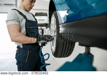 Professional Male Mechanic Screwing Or Unscrewing Car Wheel Of Lifted Automobile By Pneumatic Wrench