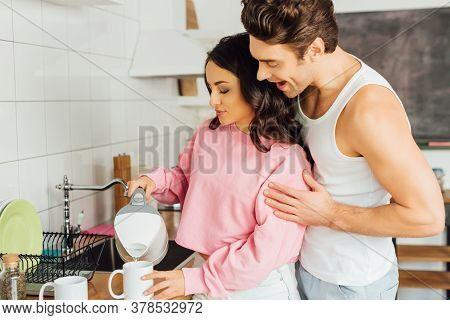 Positive Man Hugging Attractive Woman Pouring Water From Teapot In Cup On Kitchen Worktop