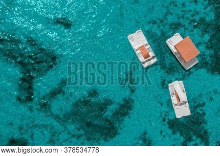 Three Catamarans On The Surface Of The Blue Sea Water Top View