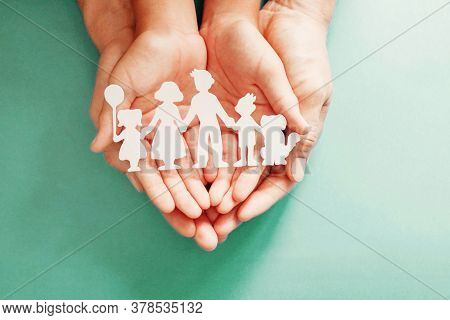 Adult and children hands holding paper family cutout, family home, adoption, foster care