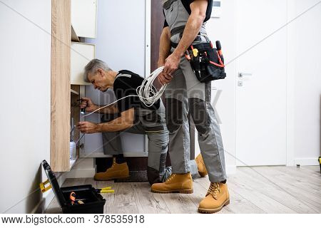 Aged Electrician, Repairman In Uniform Working, Examining Ethernet Cable Or Router In Fuse Box Using