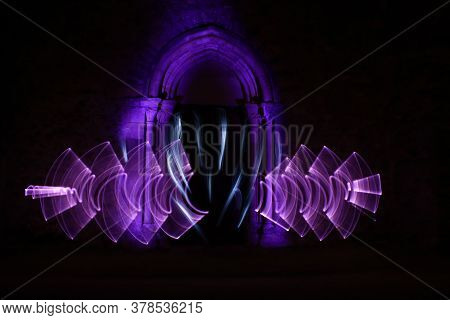 Lightpainting Scene. Abstract Shapes With A Light Saber At Night. Architecture With A Stone Arch In