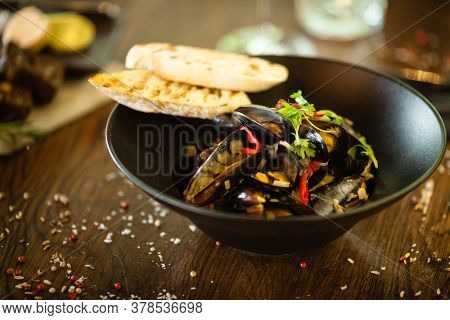 Blue mussels in white wine sauce in black bowl. Delicious healthy seafood closeup served on a table for lunch in modern cuisine gourmet restaurant.