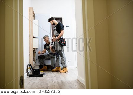 Full Length Shot Of Aged Electrician, Repairman In Uniform Working, Installing Ethernet Cable Or Rou