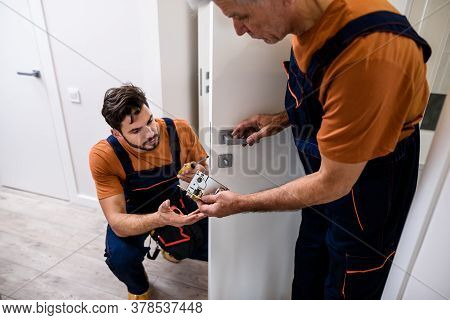 Two Locksmith, Repairmen, Workers In Uniform Installing, Working With House Door Lock Using Screwdri