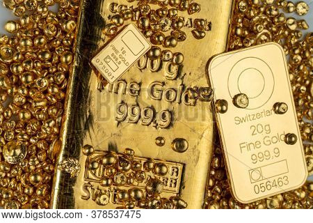 Gold Bars Of Various Weights And A Pile Of Pure Gold Granules.