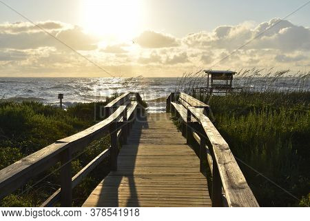 Sunrise On The Ocean, With Boardwalk And The Water In The Distance