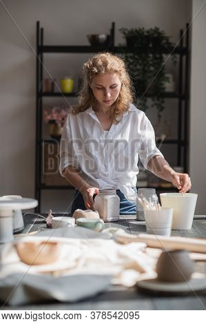 A Young European Beautiful Female Potter In A Creative Process Of Making Ceramics At Table In Worksh