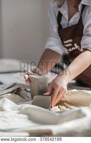 Female Potter Cutting Piece Of Pottery Clay Using Trimming Tool Close-up. Woman Use Clay Cutter To A