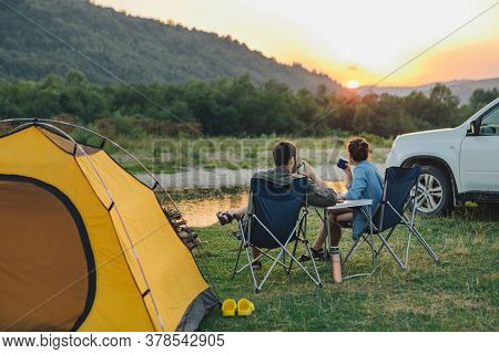 Couple Sitting In Camp Chairs Looking At Sunset Above River In Mountains