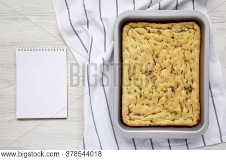 Home-baked Rosemary Garlic Focaccia Bread, Blank Notepad On A White Wooden Background, Top View. Fla