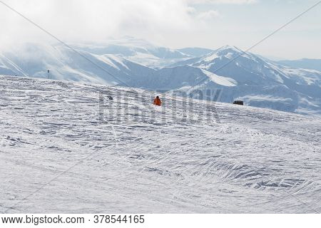 Skier Downhill On Snowy Off-piste Slope And Mountains In Haze At Sun Winter Morning. Caucasus Mounta