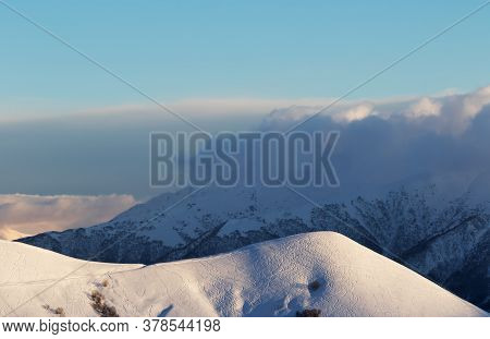 Snowy Off-piste Slope With Tracks From Skis And Snowboards. High Winter Mountains In Clouds At Eveni
