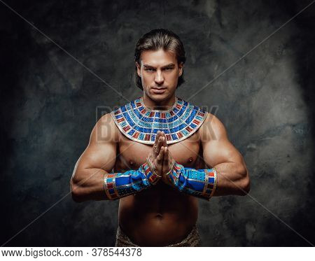 Athletic Man In Ancient Egyptian Costume Posing In The Studio With His Palms In The Sign Of Prayer