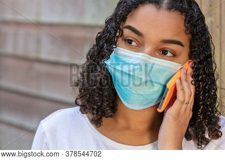 Mixed race African American teenager girl wearing a face mask and talking on mobile cell phone during the Coronavirus COVID-19 pandemic