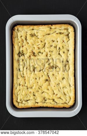 Home-baked Rosemary Garlic Focaccia Bread On Baking Tray On Black Background, Top View. Flat Lay, Ov
