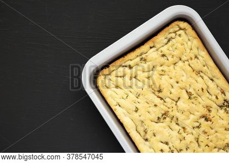 Home-baked Rosemary Garlic Focaccia Bread On Baking Tray On Black Surface, Top View. Flat Lay, Overh
