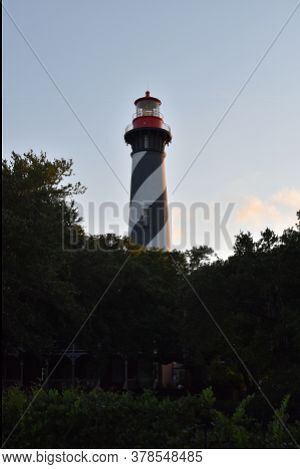 Lighthouse At Sunset Surrounded By Trees On A Warm Summer Evening. Blue Sky And Clouds.