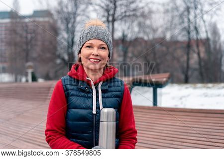 Beautiful Mature Woman Hot Holding Thermos In Park After Active Fitness Training With Friends. Activ