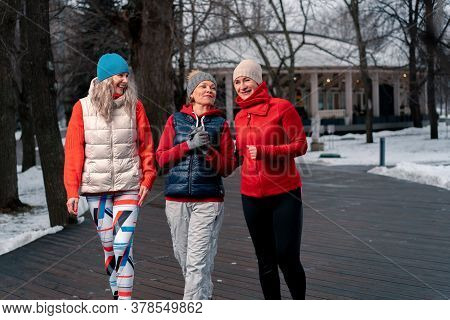 Senior Women Friends Strolling And Talking After Outdoors Training In Park. Active Lifestyle And Fri