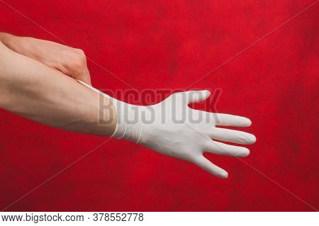 Hand In Medical Glove. Person Puts On Surgical Gloves On A Red Background