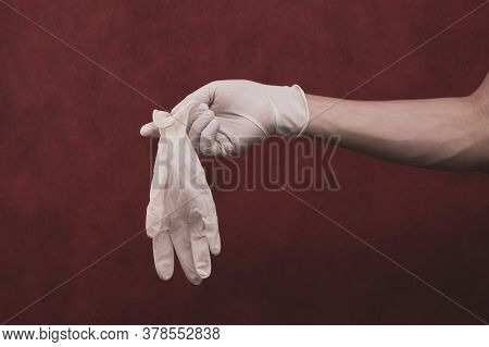 Hand In Medical Glove On A Red Background. A Person Puts On Surgical Gloves