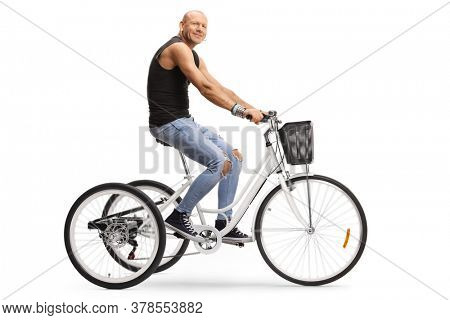 Bald hipster man riding a tricycle and looking at the camera isolated on white background