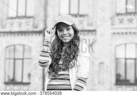 Childhood Happiness. Happy Girl With Curly Hair Wearing Cap. Child Smiling Outdoors. Beauty And Fash