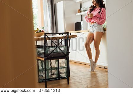 Selective Focus Of Attractive Brunette Girl Holding Coffee Cup Near Worktop In Kitchen