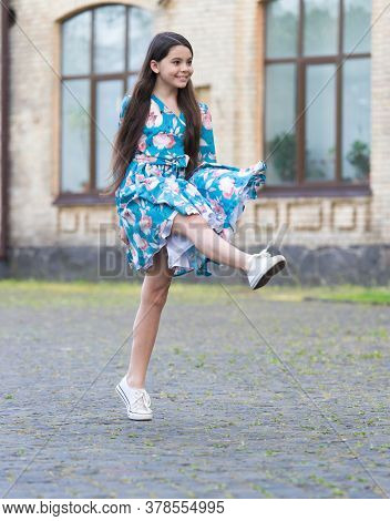 Girl Summer Dress Flutters In Motion Urban Background, Active Child Concept.