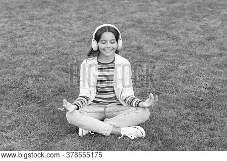 Child Doing Exercise On Green Grass. Healthy Lifestyle And Relax. Yoga Girl. Small Kid Wear Headset.