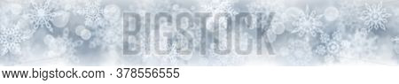 Christmas Banner Of Blurry Snowflakes On Gray Background