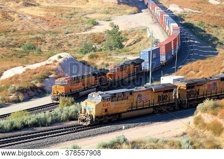 July 27, 2020 In Cajon, Ca:  Freight Train With Several Locomotives Hauling Commerce Uphill Taken In