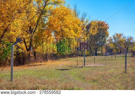 Autumn Scenery With Abandoned Basketball Court . Abandoned Sports Field In Rural Areas