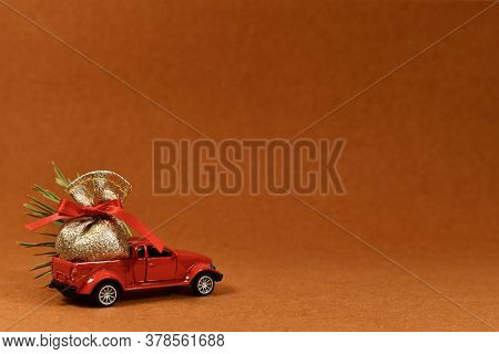 The Toy Pickup Truck Carries A Bag Of Gifts, A Christmas Tree. View Front Above, Left On A Plush Ter