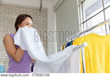Happy House Smelling The Fragrance Of The Towel On The Clothes Dryer After Laundry At Home. Househol