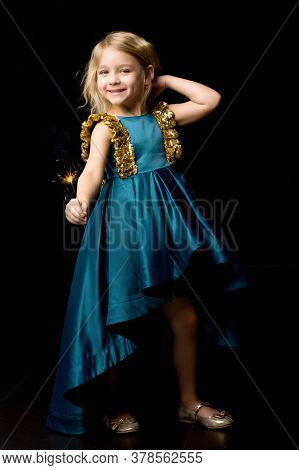 Smiling Blonde Girl Holding Burning Sparkler, Charming Girl Wearing Nice Blue Dress Looking With Adm