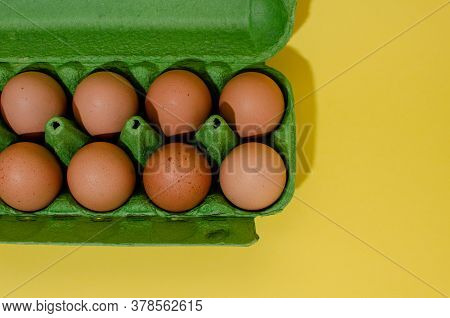 Overhead View Of Brown Chicken Eggs In An Open Egg Carton Isolated On Yellow. Fresh Chicken Eggs Bac