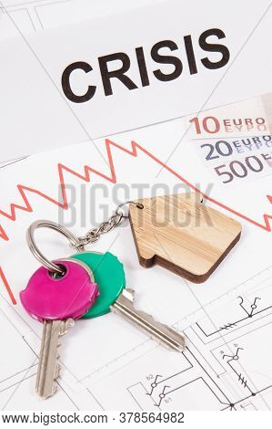 Home Keys, Inscription Crisis, Currencies Euro And Downward Graphs Representing Crisis Of Real Estat