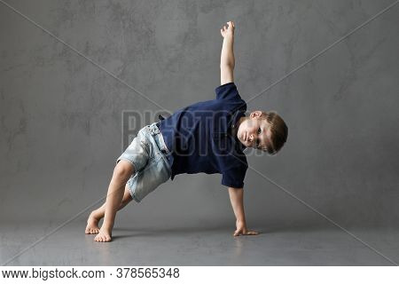 Little Boy Learns To Dance. Studio Shooting On A Gray Background. Young Boy Doing Gymnastics