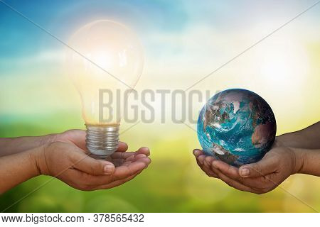 Close Up Developer Hand Holding Light Bulb And Hand Holding Blue Earth Globe Over Blurred Green Natu